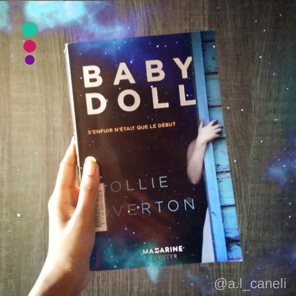 Couverture du livre Baby Doll de Hollie Overton. On y voit le bras d'une jeune femme blanche qui s'agrippe au mur d'une cabane en bois, peint en bleu.