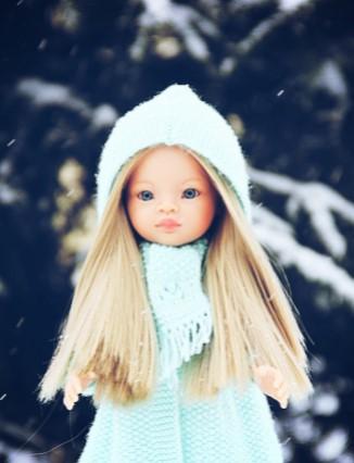 Une poupée d'enfant blonde aux yeux bleus habillée d'un manteau bleu clair en laine. Derrière elle il y a des branches de sapin lourdes de neige.