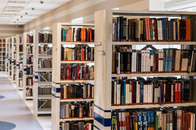 Plusieurs étagères de livres les unes derrière les autres dans une médiathèque.