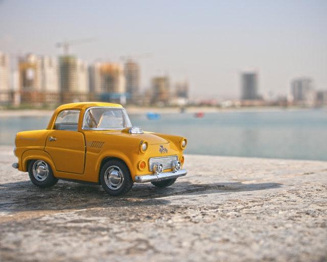 Au premier plan une petite voiture jaune. L'arrière plan est flou, on distingue des immeubles et une plage.