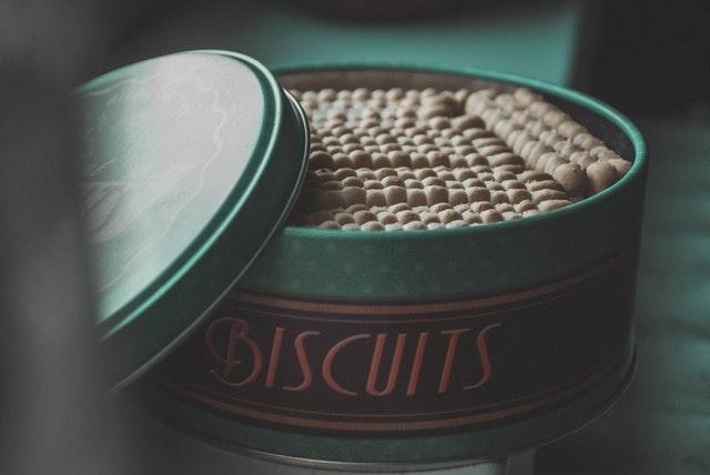 """Boîte à gâteaux en métal ronde et verte sur laquelle est écrit """"BISCUITS"""". Il y a un assortiment de biscuits à l'intérieur."""