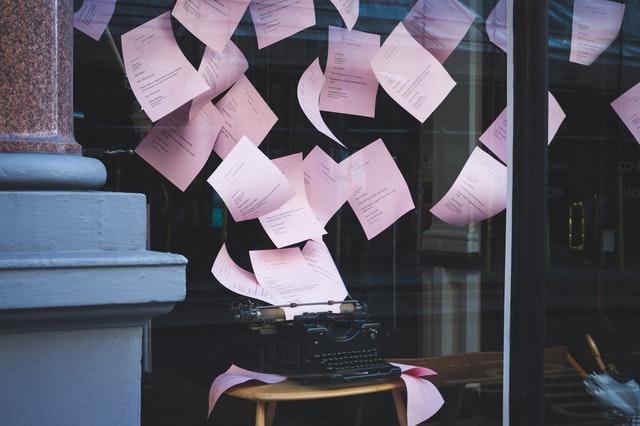 Une machine à écrire avec des feuilles roses volant autour, comme lancées en l'air,  derrière une vitrine.
