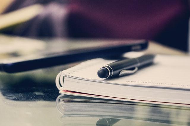 Stylo noir posé sur cahier à spirales