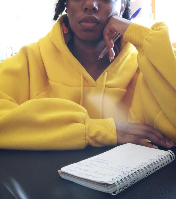 Moment de réflexion, stylo en main et main posée contre la joue, avant de se mettre à écrire.